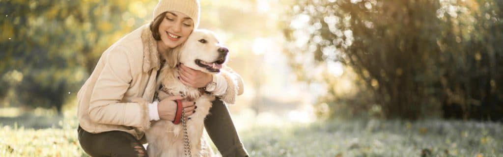 Foto de chica abrazando a perro de raza labrador.